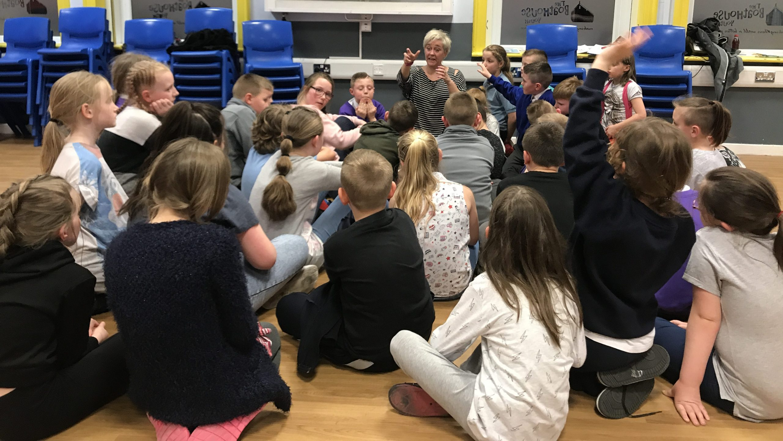 Children sat on the floor listening to Melanie speak