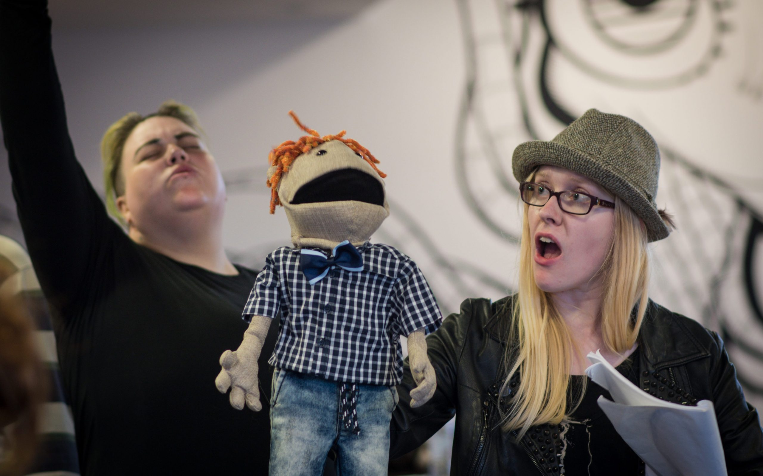 Two people performing with a ginger haired puppet