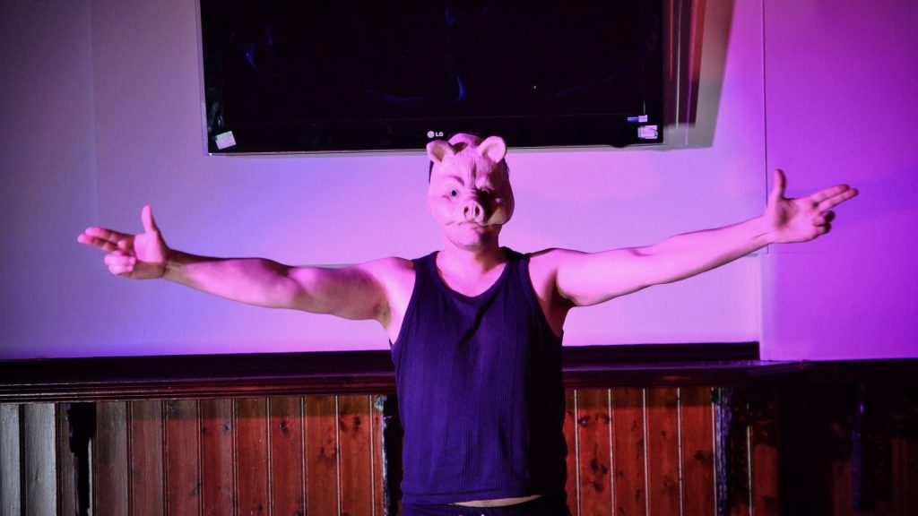 Man wearing a pig mask holding his arms out to either side - image by CJGriffiths Photography