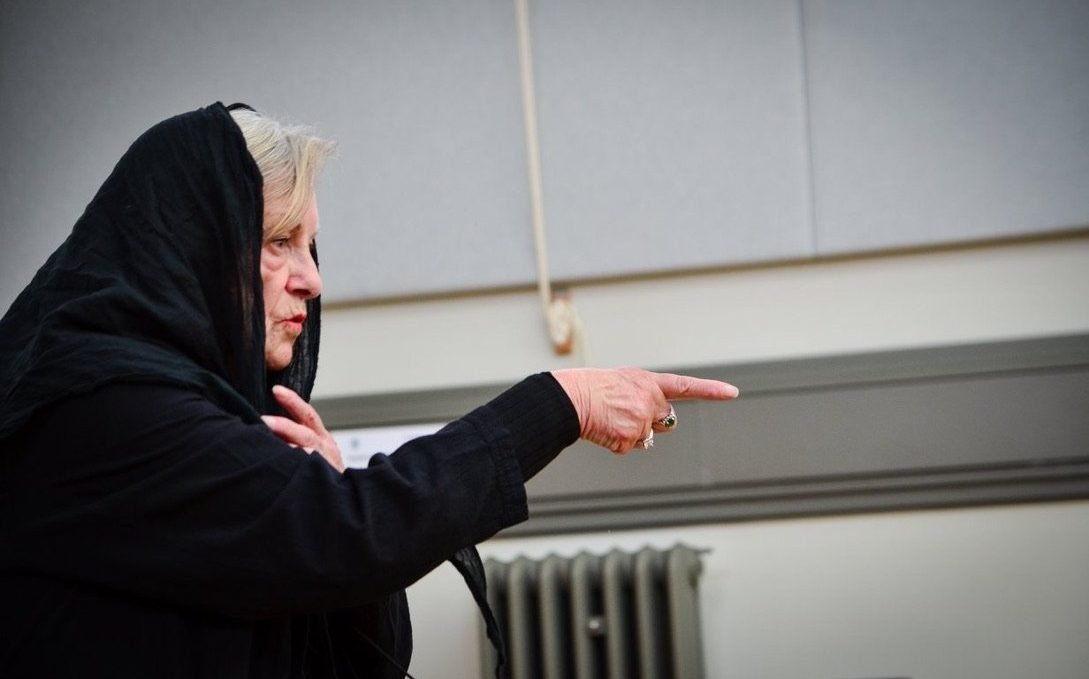 Woman in a black hooded cape, pointing
