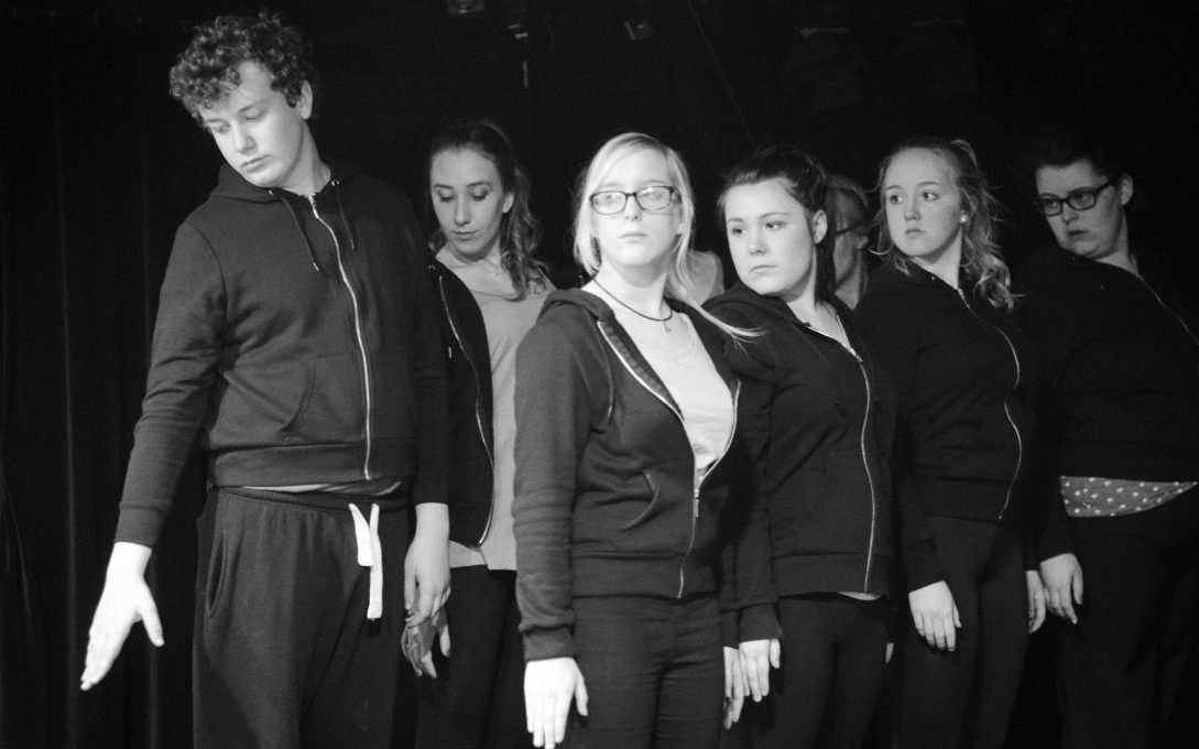 Black and white image of several young people dressed in black